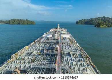 Oil tanker proceeding through Panama Canal by green dense jungle.