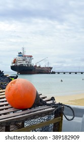 oil tanker ship at dock with lobster pot trap and buoy at Picnic Center Beach Big Corn Island Nicaragua Central America