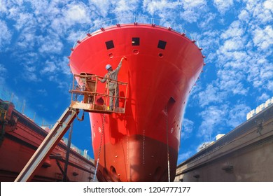 Oil Tanker Ship repair in floating dock, Worker man high work on sherry picker car during painting on side shell of front of ship in floating dry dock in shipyard Thailand on blue sky background