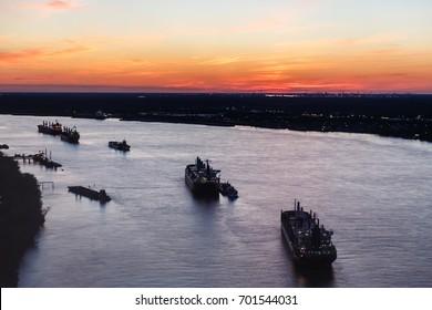 Oil tanker ships form a line along the Mississippi river at sunset