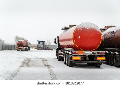 An oil tanker truck with a semitrailer-tanker truck drives through the checkpoint from the territory of the motor transport base. The picture was taken in Russia in winter