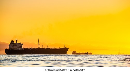 Oil tankers ship at sea on a background of sunset sky. Oil tankers in the ocean. Early in the morning, the sunrise sky. South Africa. Mossel Bay