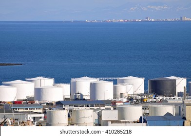 Oil tanks on seashore, with blue copy-space