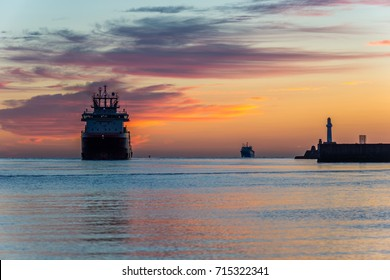 An oil tug enters Aberdeen harbour at sunrise.