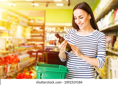 Oil for vegetable salad. Beautiful smiling young woman in casual clothes is holding a bottle of olive oil in the supermarket.