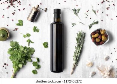 Oil vinegar bottle mockup on white wooden background, with spices, olives and blank label to place your design