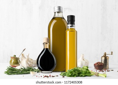 Oil and vinegar bottles composition mockup on white wooden background, with spices and blank label to place your design