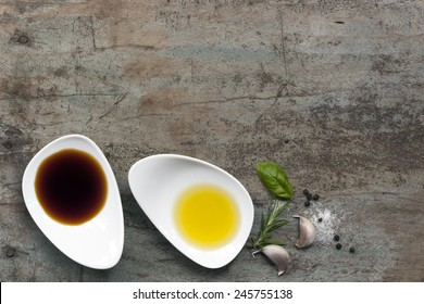 Oil and vinegar food background, with peppercorns, salt, garlic and rosemary, over grunge wood.