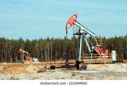 Oil well for the production of oil and gasoline and gas on the background of the forest, the production of gasoline, pumpjack, extraction of petroleum, fuel