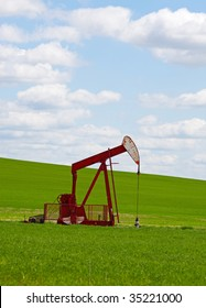 An oil well with the pump jack in action, against a grassy, green hill & cloudy blue sky.  Located in the province of Alberta, Canada.