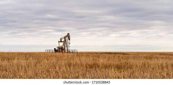 Oil Well Pump Jack pumping crude oil for fossil fuel energy. American Petroleum Oil and Gas Industry equipment extracting from a prairie in the United States of America.