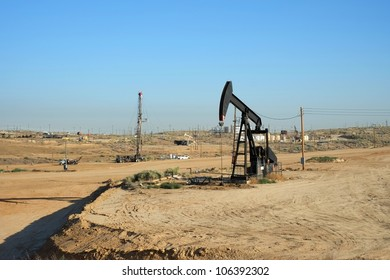 An oil well pumps crude out of the Kern County (California) fields while a servicing rig works in the background