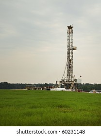 An oil well rig drilling in a Texas field with grass in the vertical format with copy space.