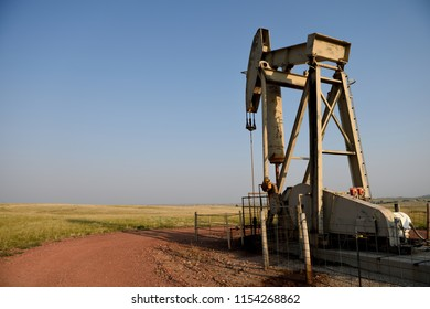 Oil well site pump jack and fields at sunset in rural Wyoming / USA.