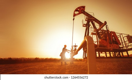 Oil worker is checking the pump near oil derrick on the sunset background.