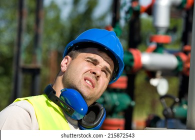 Oil worker looking up and is blinded by sun rays