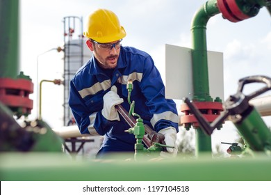 Oil worker is turning valve on the oil pipeline