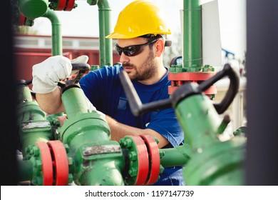 Oil worker turning valve on oil rig