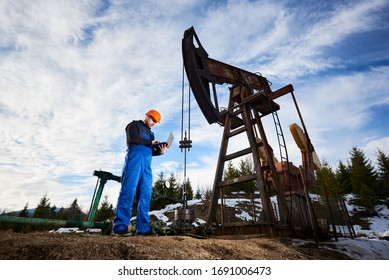 Oil worker using laptop, controlling work of petroleum pump jack. Drill operator in work overalls and helmet near oil pumping unit under cloudy sky. Concept of petroleum industry and oil extraction.