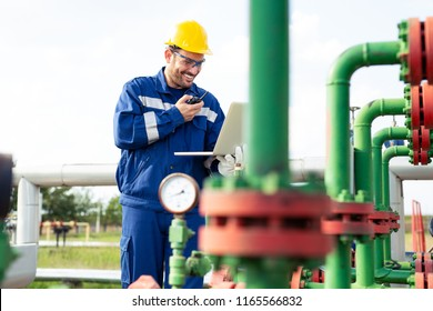 Oil worker using portable radio and laptop