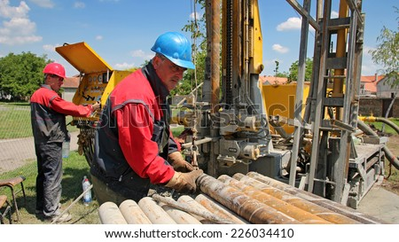 0e98acd735 Oil Workers at Work. Oil and gas industry. Oil drilling rig workers lifting  drill