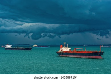 Oil/Chemical tankers anchored on outer anchorage in the Strait of Singapore under the stormy clouds.