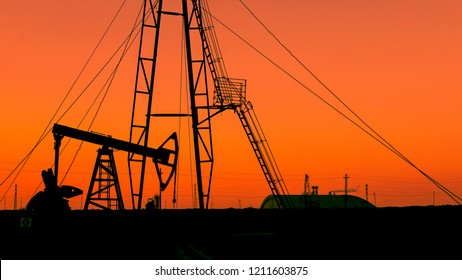 Oilfield during dark orange sunset, petrochemical industry background