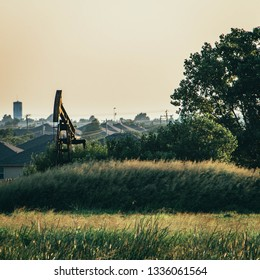 Oil-field pump jack on green grassy hill with hazy suburban neighborhood in background