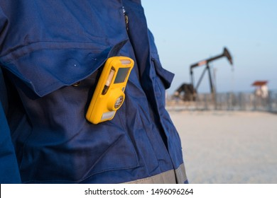 A oilfield technical worker using the H2S gas monitor in the oilfield  at job site