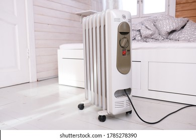 Oil-filled electrical mobile radiator heater for home heating and comfort control in the room in a wooden country house.