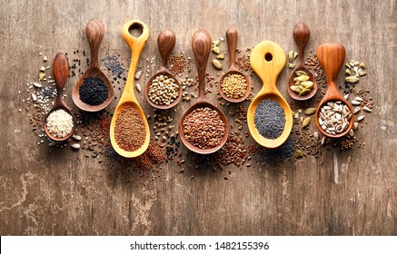Oilseeds in wooden spoon on wooden background