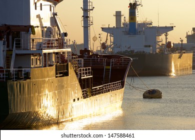 Oiltanker docking in a harbour during sunset