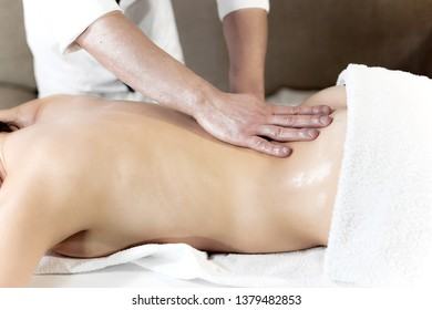 oily hands with ayurvedic oil on a woman's back