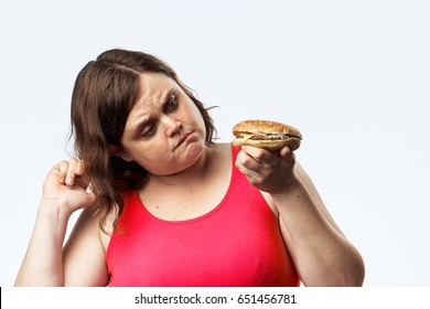 Oily woman looks thoughtfully at a hamburger