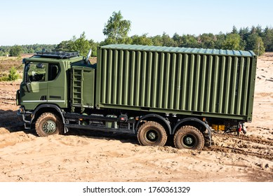 OIRSCHOT, EINDHOVEN, THE NETHERLANDS - JUNE 18, 2020: A Scania Gryphus military transport truck of the armed forces of the Netherlands is driving in the sand at the GLV-V, Oirschot.