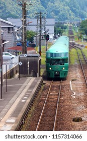 "Oita, JP - JULY 16, 2018: The vintage green romance train named ""Yufuin no Mori"" stopping at Bungomori Station, before running to Hakata Station in Kyushu."