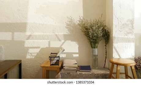 Oject ,book ,chairs , wood table and flower in bottom vase composition  and decoration living room .Sunlight through the window come to the empty wall.Life style background concept