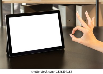 Ok gesture. Online conference. Support teamwork. Good job. Unrecognizable woman hand showing approval sign tablet computer blank screen on wooden desk workplace interior copy space.