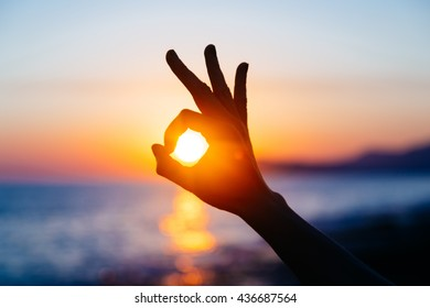 Ok hand sign silhouette at sunset
