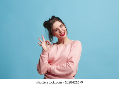 I am ok. Happy business woman, sign ok, smiling, isolated on trendy blue studio background. Beautiful female half-length portrait. Emotional woman. Human emotions, facial expression concept. Front