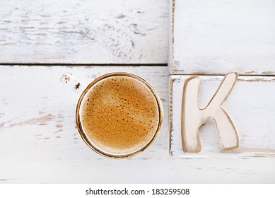 OK sign with espresso coffee in white cup and K letter,  old rustic  style table, shallow dof