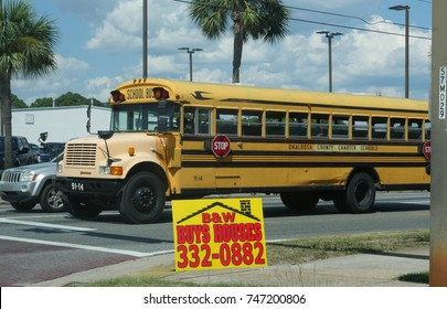 OKALOOSA COUNTY, FLORIDA—AUGUST 2015: A school bus for the Okaloosa County charter schools stop for a traffic light at an intersection. In photo is a real estate sign by the roadside.