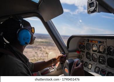 Okavango Delta, Botswana - November 18 2019: An African female pilot flies a light aircraft over the Okavango Delta in search for wildlife.