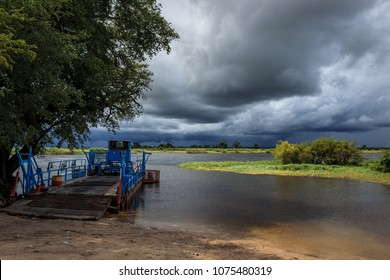 Okavango river ferry at shore with threatening storm clouds approaching