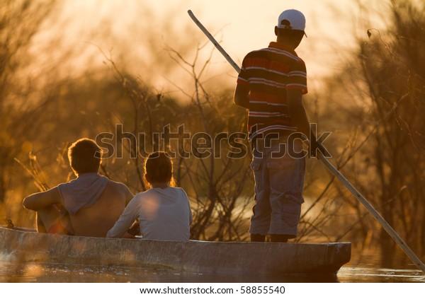 OKAWANGA DELTA, BOTSWANA - JUNE 6: Unidentified people on a traditional mocoro boat on June 6, 2010 in the Okawanga Delta, Botswana.