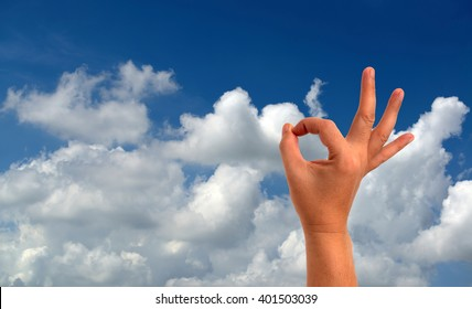 Okay hand sign on sky-clouds background.