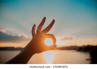 Okay hand sign silhouette at sunset