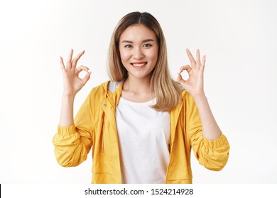 Okay perfection concept. Attractive cheerful optimistic determined asian blond girl show ok approval good gesture smiling delighted like awesome idea support agree terms, white background