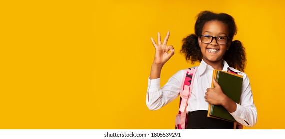 Okay, School. Cheerful African Schoolgirl Gesturing OK Holding Books Posing Over Yellow Studio Background. Panorama, Copy Space
