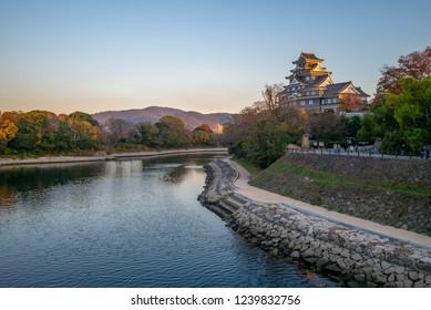 Okayama Castle by river asahi in japan at dusk